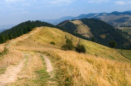 Dirt road high in the mountains that goes down to the village in the valley. The peaks of the Carpathian Mountains. Mountain ranges covered with forests under blue clouds