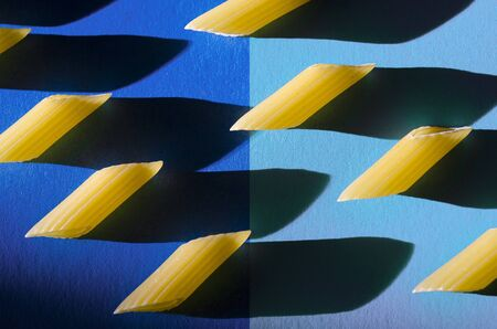Penne Pasta is a sharp shadow against a colored background. Close-up