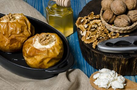 healthy food. Baked apples with cottage cheese and nuts lie in a black baking dish on a blue wooden table next to a jar of honey and a wooden board on which nuts lie. close-up