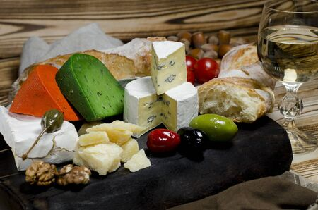 Camembert, brie, parmesan cheese, green cheese with basil and red chilli cheese lie on a dark board next to tomatoes, olives, garlic, nuts, honey, a glass of white wine and bread on a wooden table