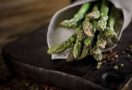 Green juicy asparagus is lying on a wooden dark board on a brown wooden table. copy space