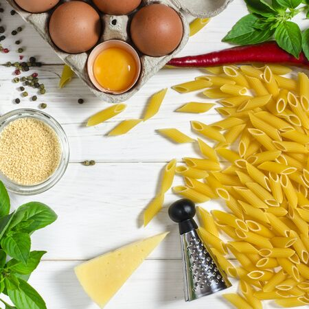 ingredients for italian cousine flat lay. Penne Pasta, green basil, parmesan, sesame, garlic, chilli, eggs lie on a white tree table. View from above Фото со стока