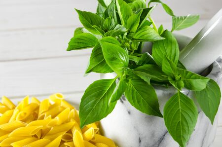 Fresh green basil in a white marble mortar on a wooden table next to pasta. Close-up
