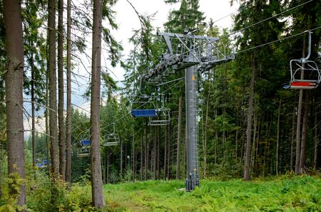 Travel concept. Couple of hikers or tourists enjoy the ride of chair lift ski lift and the beautiful mountain summer landscape with green trees and plants. Ukraine