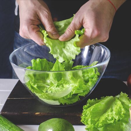 Man cooking green detox salad of romaine lettuce. Healthy food concept
