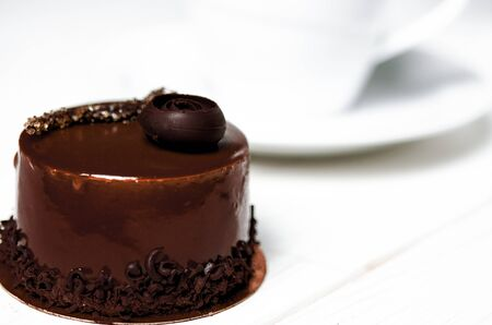 A delicious chocolate cake with chocolate pieces lies on a wooden stand next to a white cup, which stands on a white wooden table