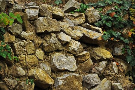 A stone wall of large sharp stones and ghee. Close-up Stock Photo