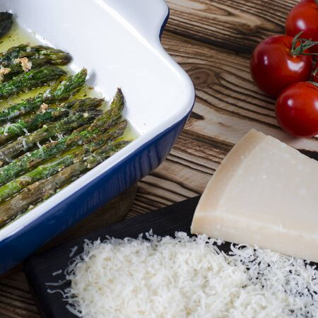 Green juicy asparagus is in ceramic form in olive oil sprinkled with parmesan and garlic.