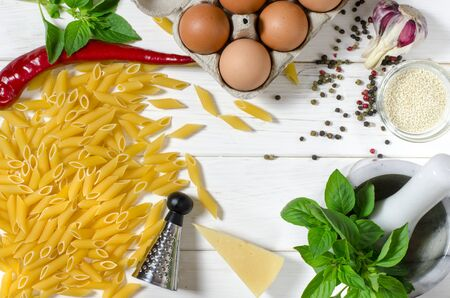 ingredients for italian cousine flat lay. Penne Pasta, green basil, parmesan, sesame, garlic, chilli, eggs lie on a white tree table. View from above Stock Photo
