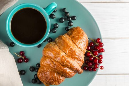 Fresh ruddy croissants with berries lie on a wooden table next to fresh black currant berries, red currants, cherries and a cup of coffee