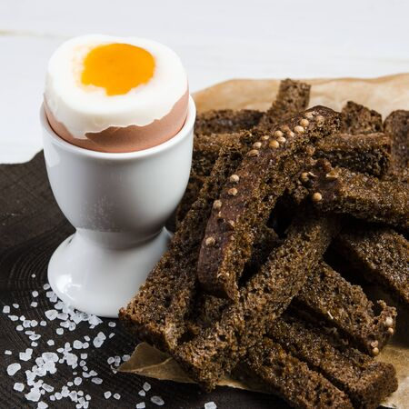 Healthy food. English breakfast with boiled egg and croutons on a white wood background. Healthy breakfast