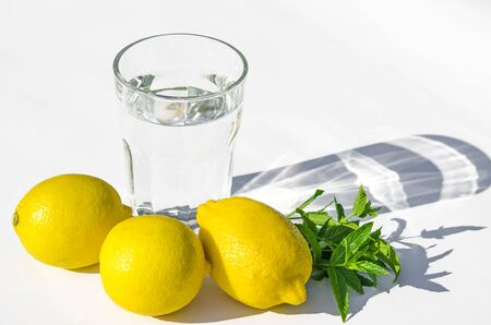 Lemons, fresh green mint and a glass glass with water on a white background. Shadows on a white background. Close-up Stock Photo