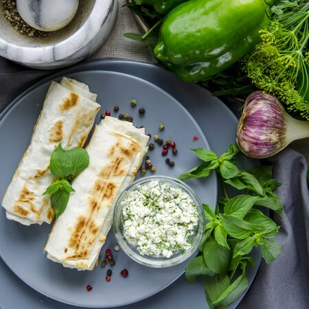 Healthy food. Healthy breakfast. Green vegetables. Pita bread with cheese and dill lie on round gray plates next to greens and a cup of coffee