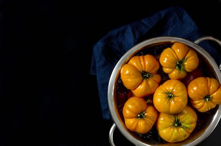 Washed various tomatoes in a colander on a black background with copy space top view