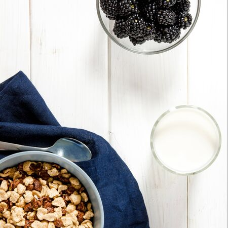 Healthy food: a healthy breakfast of cornflakes and blackberry berries on a white tree table. top view