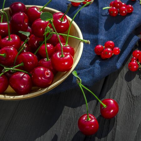 Red ripe cherry with green tails with leaves lies in a round wooden plate and red currants lies on a black wooden background