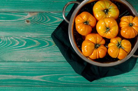 Washed various tomatoes in a colander on a wooden background with copy space top view Stock Photo