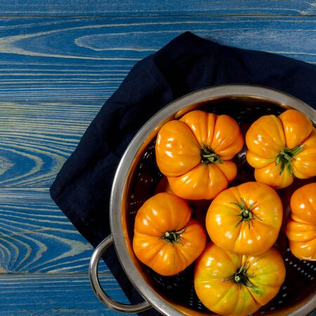 Washed various tomatoes in a colander on a wooden background with copy space top view