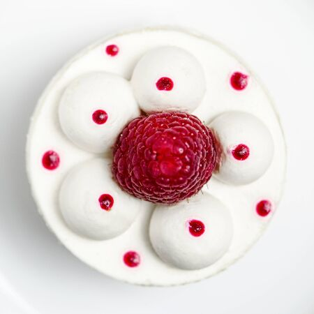 White airy cake with raspberry layer and raspberry berry lies on a white round plate next to a white cup, which stands on a white wooden table