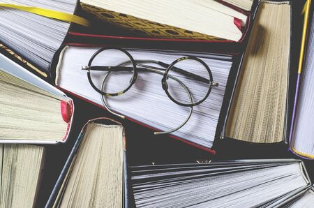 Many multicolored thick open books stand on a dark background. On the books are old round glasses and an open notebook with a pencil. ready to read 写真素材
