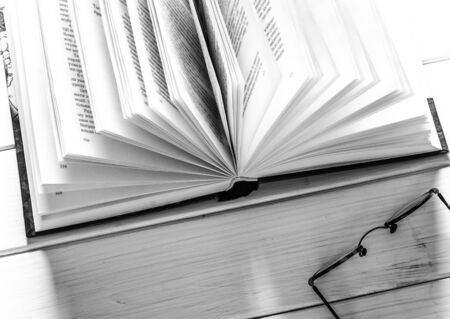 Open book ready to read lies on a white wood table next to the old round glasses. closeup 写真素材 - 128616646