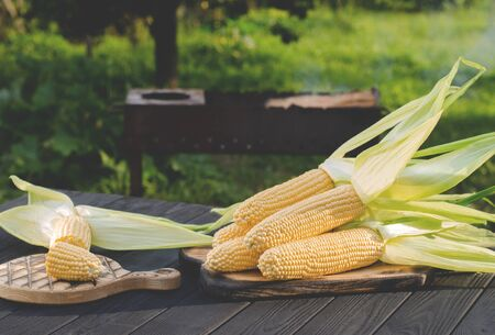 Yellow juicy corn with green leaves lies on a wooden table in the summer garden against the backdrop of a grill