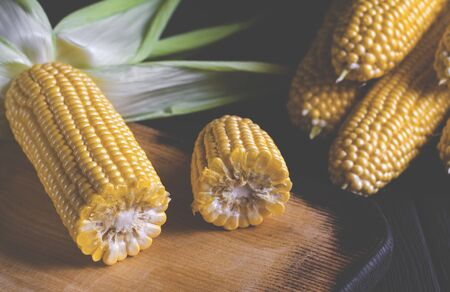 Yellow juicy corn with green leaves on a black tree table. Close-up Фото со стока