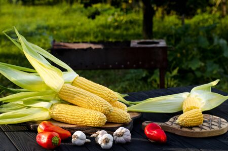 Yellow juicy corn with green leaves lies on a wooden table in the summer garden against the backdrop of a grill. Ready to cook Stockfoto - 128616722