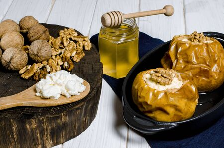 Baked apples with cottage cheese and nuts lie in a black baking dish on a white wooden table next to a jar of honey and a wooden board on which nuts lie. close-up Stockfoto