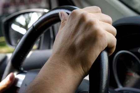 Close up shot of a mans hands holding a cars steering wheel Фото со стока