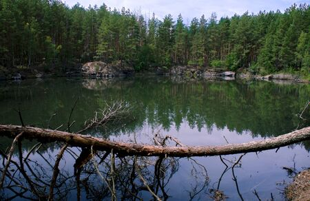 Coniferous forest is reflected in a lake with granite shores against the blue sky Фото со стока