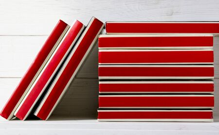 Many red-bound books stand on a white wooden shelf. Ready to read