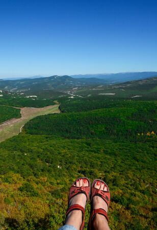 womens feet with red pedicure in red sandals over a high cliff against the backdrop of mountains and blue sky Фото со стока