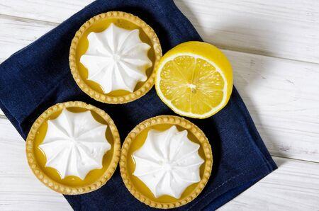 Lemon Meringue Pie. Small Lemon Meringue Pie Dessert Shortcrust Pastry with Lemon Custard Filling and Fluffy Meringue Topping Isolated on a white background. Selective focus.