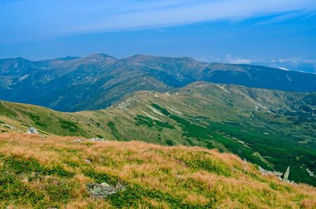 The high mountain range is overgrown with green and yellow grass against the blue sky with clouds. Hiking in the mountains 写真素材