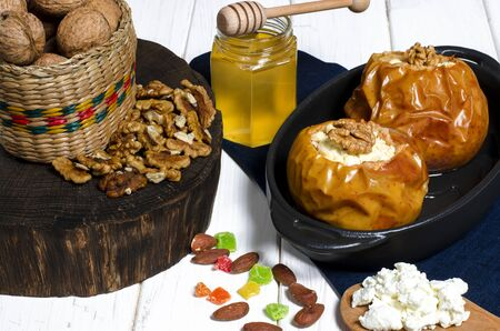 Baked apples with cottage cheese and nuts lie in a black baking dish on a white wooden table next to a jar of honey and a wooden board on which nuts lie. close-up Zdjęcie Seryjne