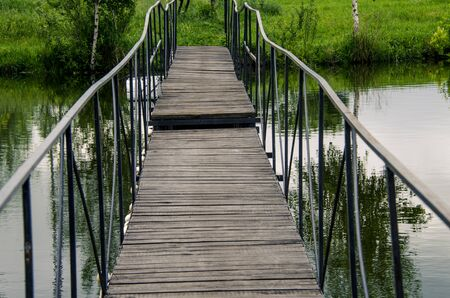 A narrow wooden bridge with a metal railing leads across the river to the shore with green grass