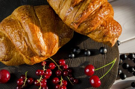 Fresh ruddy croissants with berries lie on a wooden table next to fresh black currant berries, red currants, cherries and a glass of water 版權商用圖片