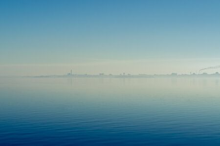The city in a fog with smoking pipes is reflected in the water against the blue sky. Ecology Фото со стока