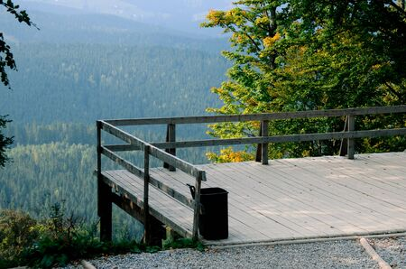 A wooden observation deck over a cliff overlooking the mountain slopes covered with ancient forests. Landscape Фото со стока