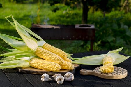 Yellow juicy corn with green leaves lies on a wooden table in the summer garden against the backdrop of a grill. Ready to cook