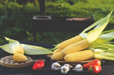 Yellow juicy corn with green leaves lies on a wooden table in the summer garden against the backdrop of a grill. Ready to cook 스톡 콘텐츠 - 129248127