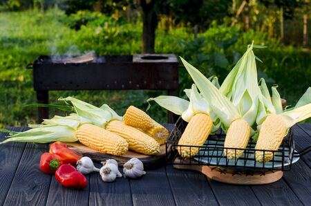 Yellow juicy corn with green leaves lies on a wooden table in the summer garden against the backdrop of a grill. Ready to cook 스톡 콘텐츠 - 129248133