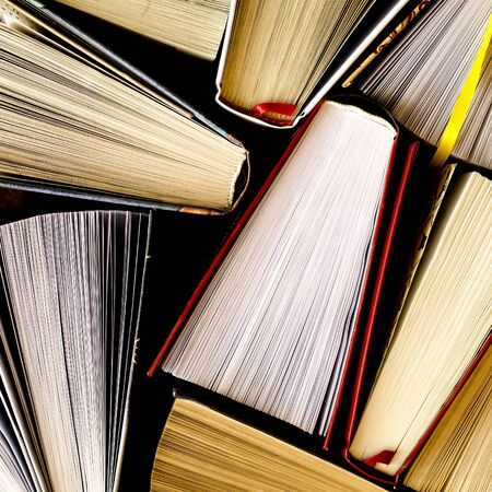 Lots of colourful thick open books stand on a dark background. ready to read