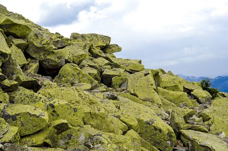 Huge stones with green lichen lie on top of the mountain against the backdrop of high ridges and blue sky