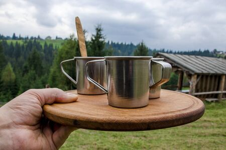 A mans hand holds a tray with three cups of coffee on a wooden board against the background of the forest and mountains