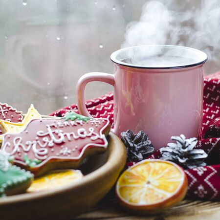 Christmas card: A cup of hot tea stands on a wooden table next to a wooden plate on which are gingerbread cookies made from orange slices against the background of a window with water drops Фото со стока