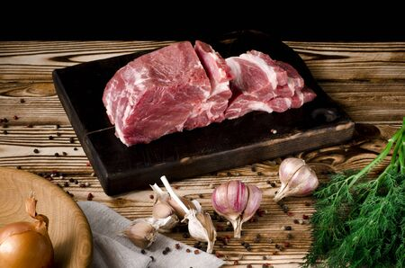 Man slicing pork on wooden board at restaurant kitchen. Chef preparing fresh meat for cooking. Modern cuisine backgroung with herbs and vegetables vegetables
