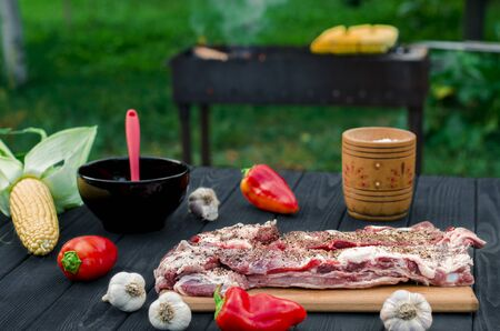 Pork ribs in a marinade lie on a wooden table in the garden next to pepper, garlic, corn on the grill background. Ready to eat Imagens