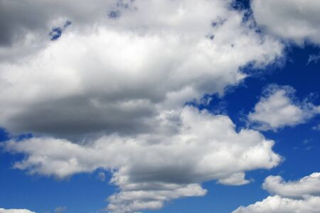 White fluffy clouds in a dark blue sky. Heavenly background Stock Photo